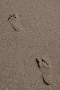 two barefoot footprints on a sandy beach