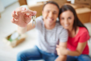 Hand of young man showing keys from new flat